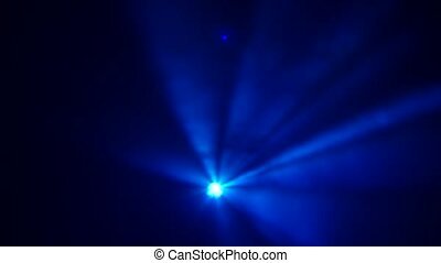 Searchlight with multi colored light in smoke on a black...