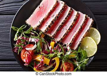 Seared ahi tuna coated sesame seeds with salad on black plate closeup. Top view horizontal
