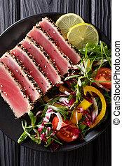 Seared ahi tuna coated sesame seeds with salad on black plate closeup. Top view vertical