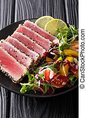 Seared ahi tuna coated sesame seeds with salad on black plate closeup. vertical