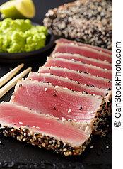 Seared ahi tuna coated sesame seeds with wasabi macro. Vertical