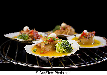 seared scallops with broccoli on black background.