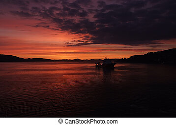 Seascape after sunset in Bergen, Norway. Ship in sea in evening dusk. Dramatic sky over sunset sea water. Traveling with adventures by ship. sunrise. Beauty of nature. Wanderlust and vacation