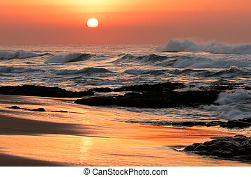 Seascape at sunrise with golden reflections and rocks in foreground
