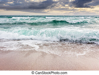seascape in stormy weather at cloudy sunrise. green waves...