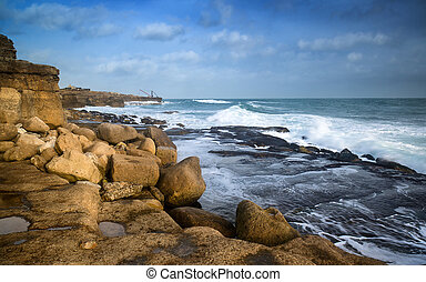 Seascape landscape of waves crashing onto rocks during beautiful Winter's day