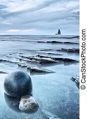Seascape of rocks and sea at sunset. A round stone in the...