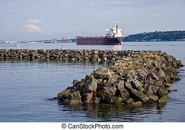 Seascape on Puget Sound of cargo ship and rock jetty, Mount Rainier in distance.