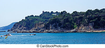Seascape panorama near Lloret de Mar, Costa Brava, Spain. Fast moving boat in fram