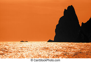 Seascape - Silhouettes of rock and ship on flashing orange ...