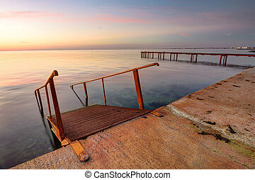 Seascape, staircase descends into the sea, on the far side of the pier