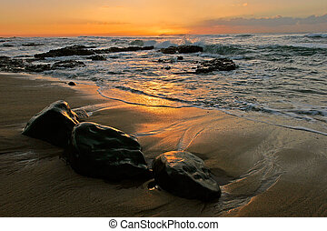 Seascape at sunrise with rocks in foreground