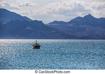 Seascape with a boat and mountains