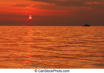 seascape with a boat on the background of sunset
