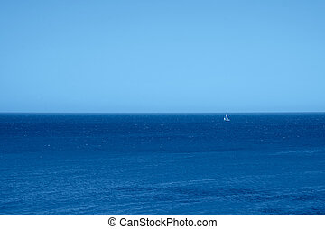 Seascape with a lonely sailingship in the trendy classic blue color of the year.