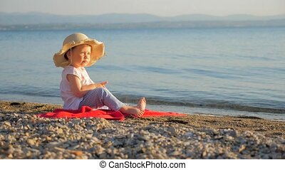 Seascape with baby eyes. Little girl sitting on the coast and looking on seascape. Summer vacation background. Childhood concept. Travel agency background. Tourists places.