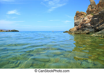 Seascape with cliff, clear water and blue sky