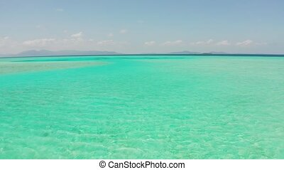 Atoll with coral reef and turquoise water against the sky with clouds top view. Summer and travel vacation concept. Balabac, Palawan, Philippines