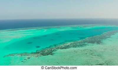 Tropical coral atoll with turquoise water against the sky with clouds top view. Summer and travel vacation concept. Balabac, Palawan, Philippines