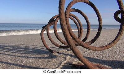 Seascape with old rusty metal spring stuck in the sand