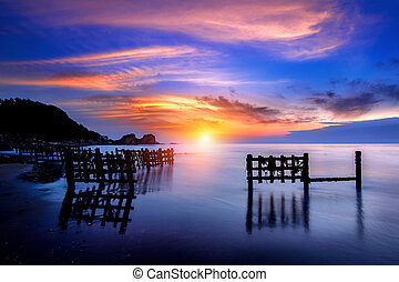 seascape with row of wood at sunset