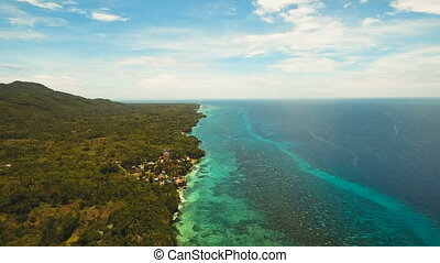 Seascape with tropical island, beach, resort, hotels. Bohol, Anda area, Philippines.