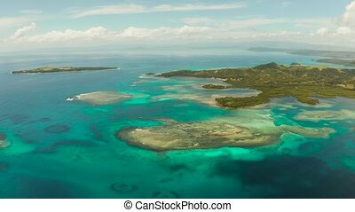 Coral atoll with blue water and a tropical island in the ocean on a sunny day. Bucas grande, Philippines. Summer and travel vacation concept.