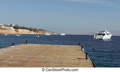 Seascape with wooden pier against the background of white yacht floats