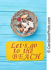 Seashells in decorative wooden basket.