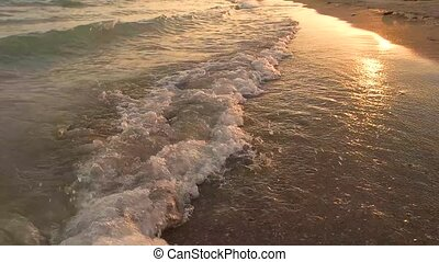 Seashore at sunset, slow-mo. Small foamy waves. Paradise...