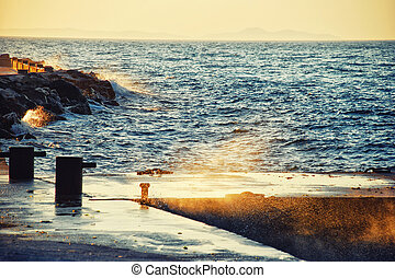 Seashore dock at sunset with waves