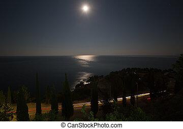 Seashore highway, sky and moon at night