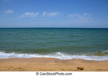 Seashore in summer, with clouds in the sky, with waves