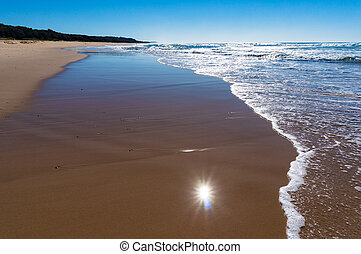 Seashore low angle shot with sun reflection in water -...
