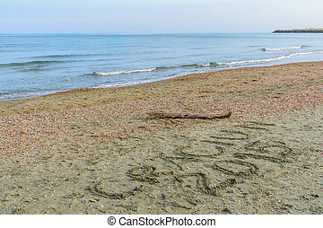 """Seashore, sand and water with Christmas message written. Sea water and sand with shells with """"Craciun 2015"""" written on it."""