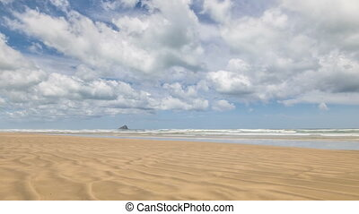 White clouds moving over sunny beach in beautiful summer day in Ninety mile beach in New Zealand. Time Lapse, Dolly shot, Panoramic.