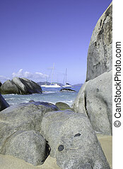 Sailboats can be seen behind giant boulders on the beach in Virgin Gorda, British Virgin Islands