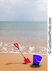 Bucket and spade on a sandy beach.