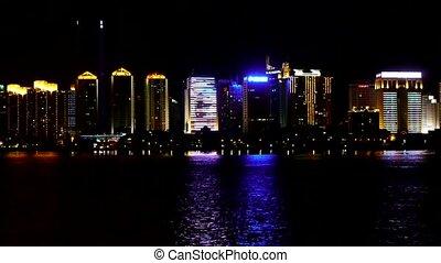 Seaside city at night, skyscrapers