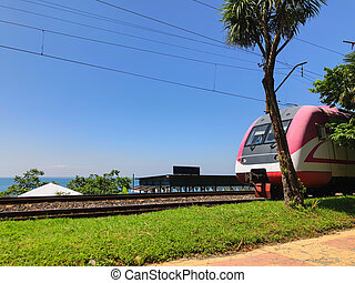 Seaside city, railway, moving passenger train on the railroad at summer day. Industrial landscape. Transport