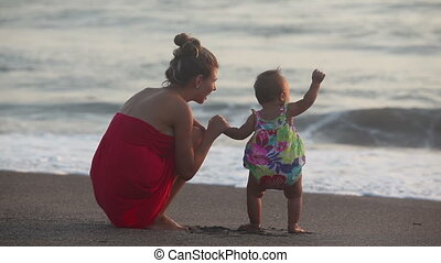 Seaside   - Mother showing to toddler summer sea