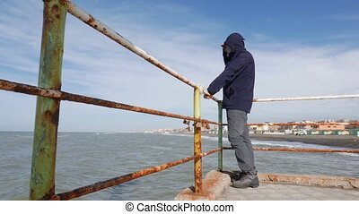 seaside pier - Mature man and the sea on a sunny windy day