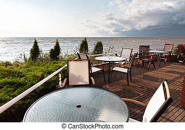 Seaside recreation area with glass tables, juniper bushes and clouds in the evening sky