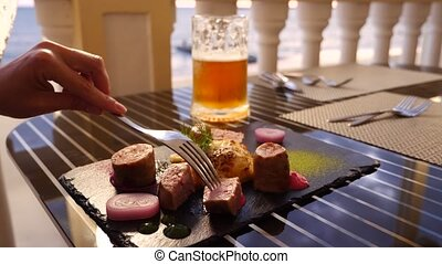 Seaside restaurant. A woman eats meat and drinks beer in a...