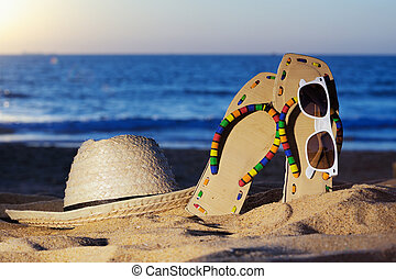 Seaside - Wicker hat, sandal and glasses on the sandy beach