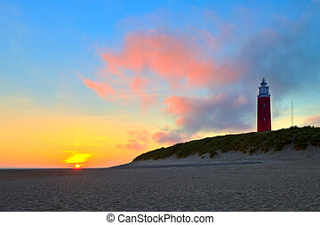 Seaside with sand dunes and lighthouse at sunset