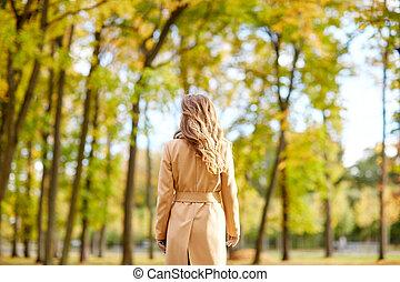 beautiful young woman walking in autumn park