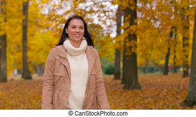 happy young woman walking in autumn park