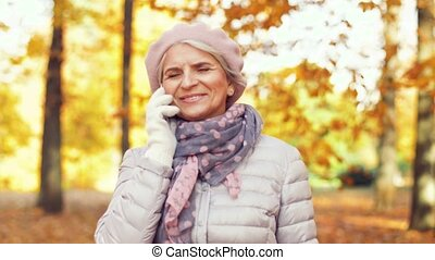 senior woman calling on smartphone at autumn park - season,...