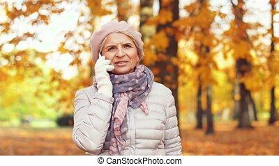 senior woman calling on smartphone at autumn park - season,...